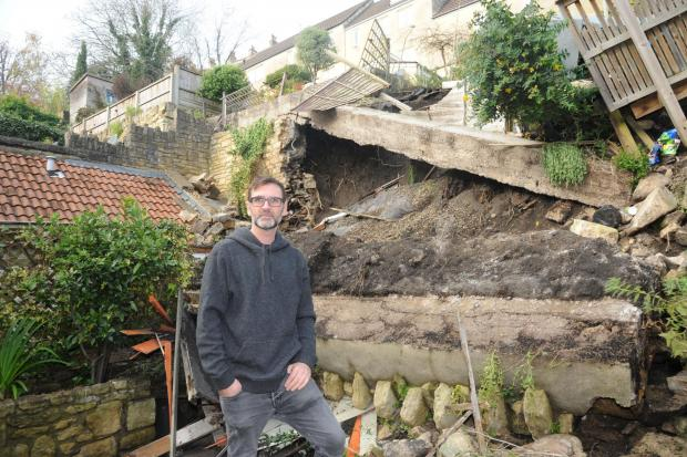 Cumberland & Westmorland Gazette: RUBBLE: Damien Weddell at his newly purchased home in Bradford on Avon where his garden wall has collapsed